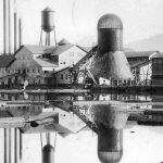 Large Agricultural Structure Reflected in the Water With Smokestacks and Woods in the Background Black and White