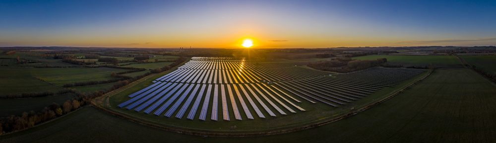 Aerial Photo of Solar Panels on a Farm and Sunset in the Background