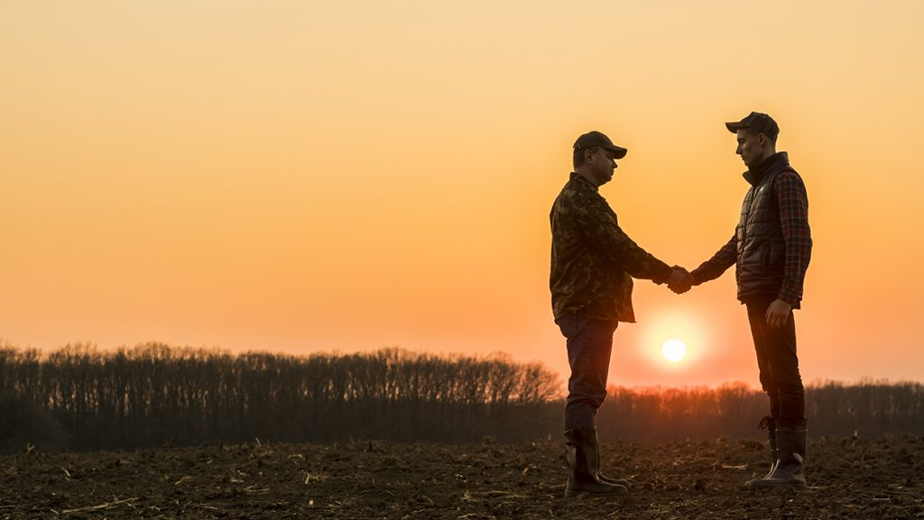farmers-shaking-hands-sunset