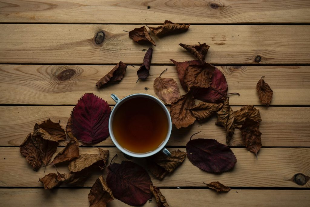 A cup of compost tea on a wooden table with autumn leaves.