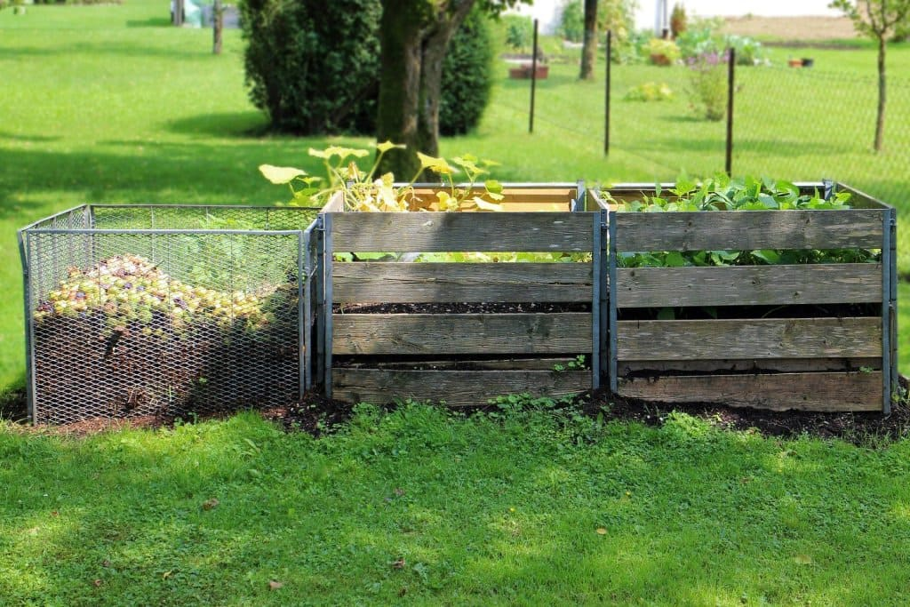 Three bays for making compost in a grassy field.