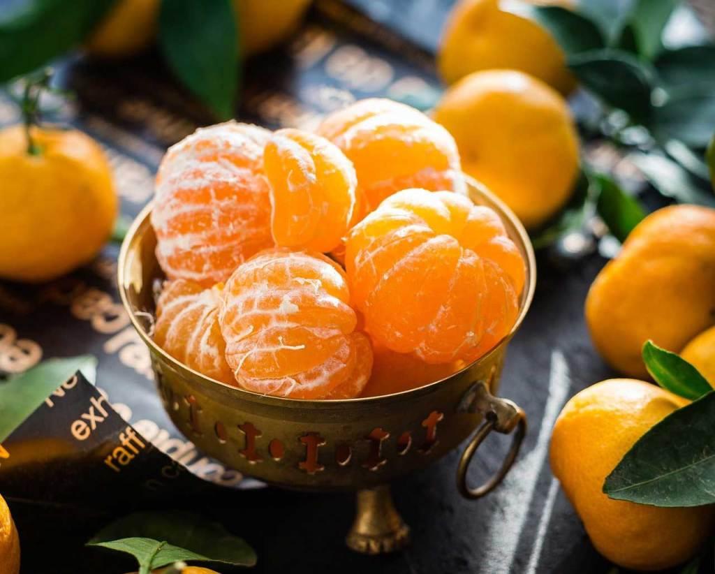Peeled mandarins in a metal bowl.